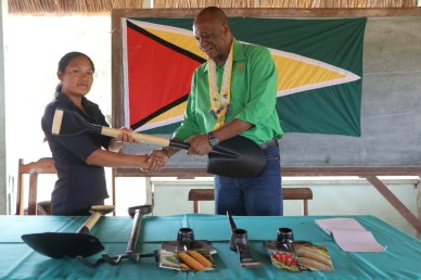 Minister of State, Joseph Harmon hand over farming equipment to another resident of Achiwib