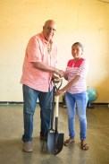 Managing Director of Guyana Water Incorporated (GWI), Dr. Richard Van West-Charles hands over farming equipment to a resident