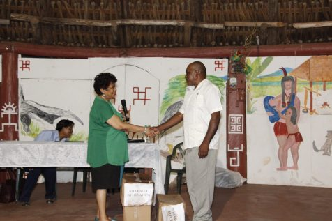 Minister of Social Protection, Amna Ally presents boxes of footwear to Toshao, S. Ignatius, Allan Ambrose