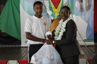 Minister of Education, Dr. the Hon. Nicolette Henry handing over the sports gears to a student of Canje Secondary School