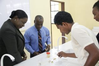 Minister of Education, Dr. the Hon. Nicolette Henry and the Headteacher of the Vryman's Erven Secondary School along with students conducting an experiment in the new laboratory