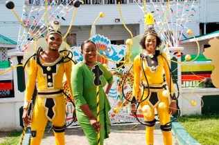 Minister of Education, Dr. the Hon. Nicolette Henry posing with the male and female models wearing the Ministry's reveller costumes.