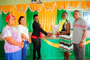 An official from the community library accepting the books from Minister Henry. (Ministry of Education photo)