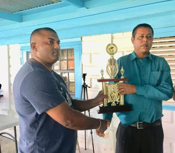 Officer in Charge of Number Two Sub Division, Mahendra Singh accepts the trophy from President of the Upper Corentyne Chamber of Commerce, Mohindra Persaud