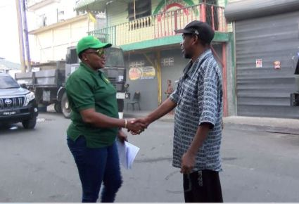 Minister within the Ministry of Public Infrastructure, Annette Ferguson greets a resident.