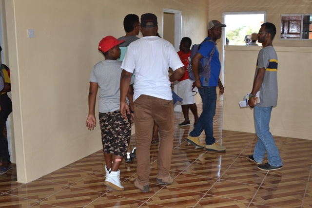 Several persons gathered at one of the houses as they checked out the interior designs