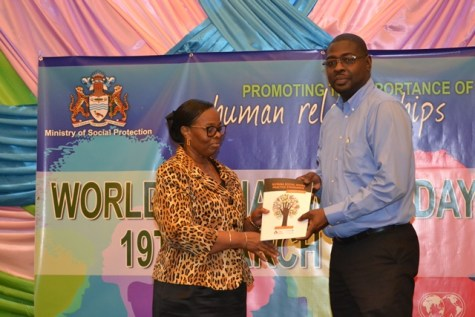 Director of Social Services attached to the Ministry of Social Protection, Wentworth Tanner handing over a copy of the first Social Work Practice Standard to Deputy Permanent Secretary, Loraine Baird.