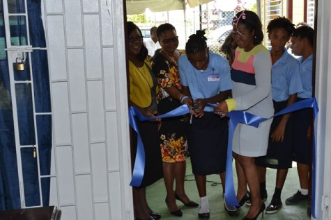 One of the students cutting the ribbon of the beauty centre in the presence of the Ministers of Public Health and the Director of Disability and Rehabilitation Services.