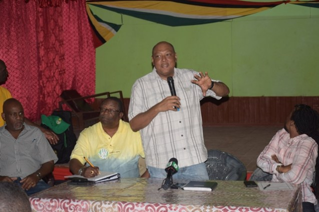 Minister of Natural Resources, Raphael Trotman speaking with residents of Kwakwani at the community's workers' club which is earmarked for renovation. Accompanying the minister to the meeting were Members of Parliament, Jermaine Figueira [right] and Audwin Rutherford [left].