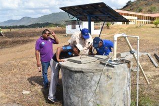 GWI officials inspecting a well with a Toshao.