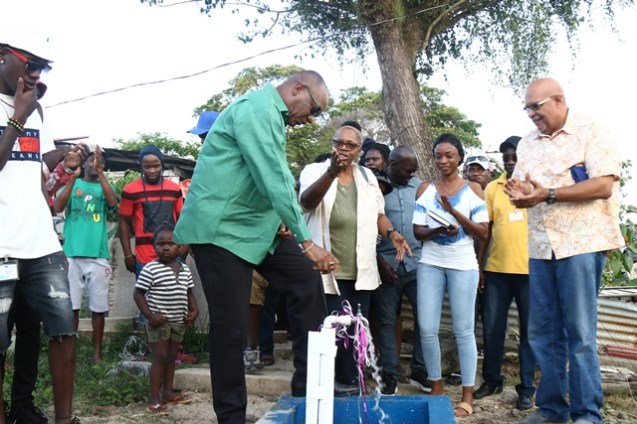 Minister of State, Joseph Harmon and Dr. Richard Van West-Charles turns on one of the 29 standpipes in the community as residents watched on.