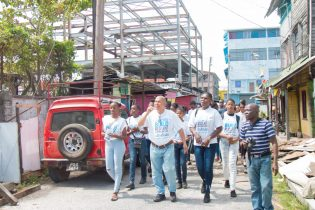 Minister of Social Cohesion Dr. George Norton along with his team of youth volunteer walking around Tiger Bay community
