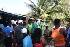 Minister of State, Joseph Harmon greets residents upon his arrival at a resident's home.