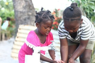 Happy children taking a taste of the clean and safe water.