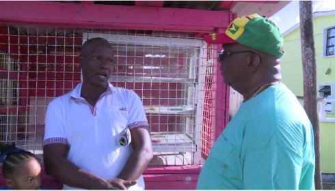 Minister of Finance, Winston Jordan listens to a resident of West Ruimveldt.