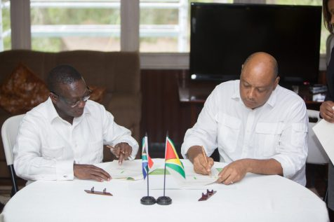 "Minister of Natural Resources, Raphael Trotman and South Africa's Deputy Minister of Mineral Resources, Godfrey Oliphant signing the ""Declaration of Intent"" at Watooka House in Linden"