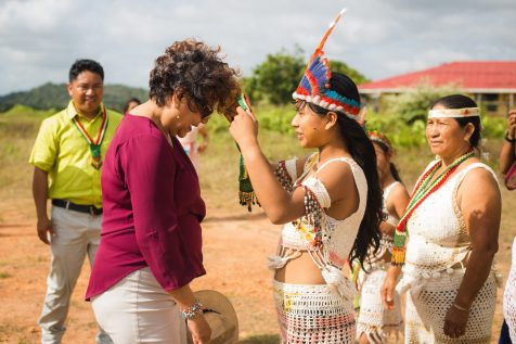 Minister within the Ministry of Indigenous Peoples' Affairs, Valerie Garrido-Lowe being welcomed by a young Indigenous girl of Aishalton Village, Region 9
