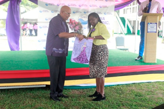Minister within the Ministry of Communities, Hon. Valerie Patterson-Yearwood being presented with an International Women's Day gift by GWI's Managing Director, Dr. Richard Van West-Charles.
