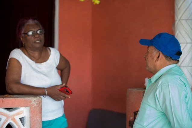 Minister of Indigenous Peoples' Affairs, Sydney Allicock interacting with a resident of East La Penitence, Ingrid Lowe.