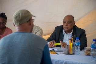 """Minister of Natural Resources, Raphael Trotman listens attentively to Prince Bowman from West Coast Berbice during today's """"Bringing Govt to the people"""" initiative, at the Square of the Revelation."""