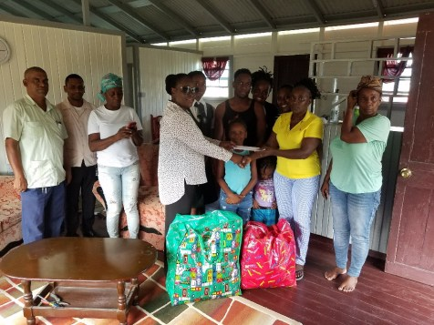Regional Executive Officer Jennifer Ferreira Dougall [fourth from left)] making the presentation to Zonipetra Austin as her family looks on