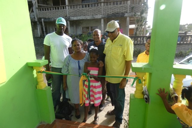 June Allicock [left] assisting the youngest granddaughter in her care to cut the ceremonial ribbon while Minister of Natural Resources, Raphael Trotman [right] and other AFC executives look on.