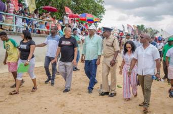 Minister of State, Joseph Harmon and Regional Chairman, Gordon Bradford and other officials stroll along the beach.