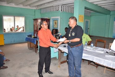 Rincon Senior Councillor, Zebedee Williams receiving a cheque from Minister of Indigenous Peoples' Affairs, Sydney Allicock.
