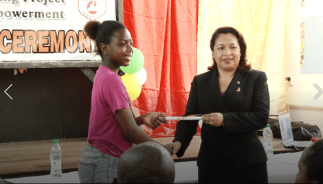 Minister of Public Affairs, Dawn Hastings Williams presents one of the graduates with her certificate.