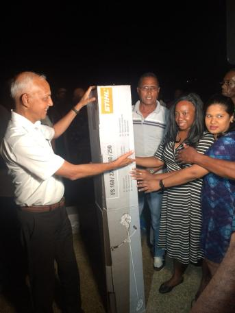 Minister of Communities, Ronald Bulkan handing over a brush cutter to Deputy Head Mistress of Crabwood Creek Primary, Aileene Davidson and Teacher Waheeda Hussain.