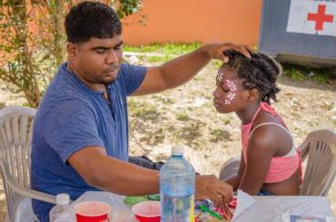 Courtney Douglas paints the face of one of his young customers.