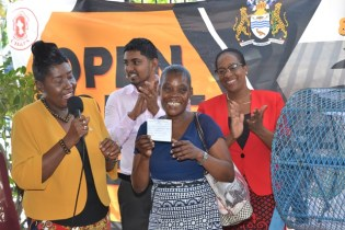 An elated Ayasia May LaFleur holds up the winning lottery ticket while Minister within the Ministry of Communities with responsibility for Housing, Valarie Adams Yearwood and staffers look on.