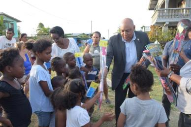 Minister of Natural Resources, Raphael Trotman distributing kites to the children of Plastic City, Vreed-en-Hoop, West Coast of Demerara (WCD).