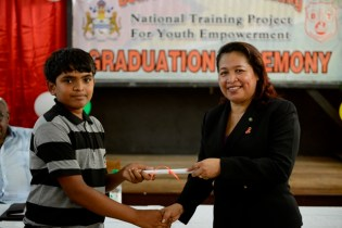 Minister of Public Affairs, Dawn Hastings-Williams handing out a certificate to one of the beneficiaries.