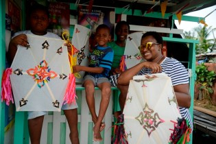 Young people smiling with their kites alongside Minister within the Ministry of Public Infrastructure, Annette Ferguson on West Ruimveldt Front Road.