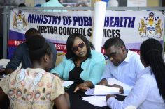 Junior Minister of Health Karen Cummings and Chief Medical Officer Shamdeo Persaud assist a resident with her necessary paper work