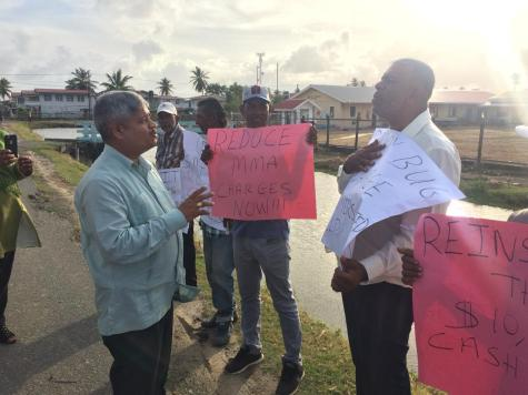 A government for all the people: Minister within the Ministry of Finance, Jaipaul Sharma interacting with some of the protestors outside of the meeting at the Latchmansingh Primary School.