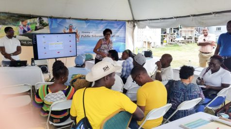 Minister of Public Telecommunications, Catherine Hughes giving a demonstration of the app to farmers
