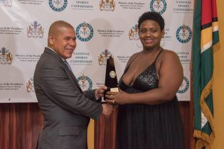 Mother of Stanton Rose Jr. accepting his award for Senior Sportsman of the year from Minister of Social Cohesion, with responsibility for Culture, Youth and Sport, Dr. George Norton.