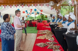 [In the photo, from right to left] British High Commissioner, Greg Quinn and Vice Principal, Myrna Lee tasting some of the cuisines on display at a Tea Party held at the British High Commissioner's residence.