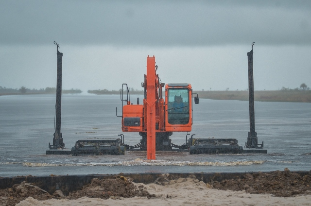 The amphibious excavator as it pushes off from shore, anchors raised.