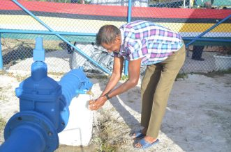 Naamless Resident washing hand under pipe in newly recommissioned Hubu water station