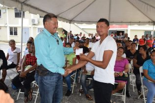 Minister of Indigenous Peoples' Affairs, Sydney Allicock handing over the grant to one of the entrepreneurs