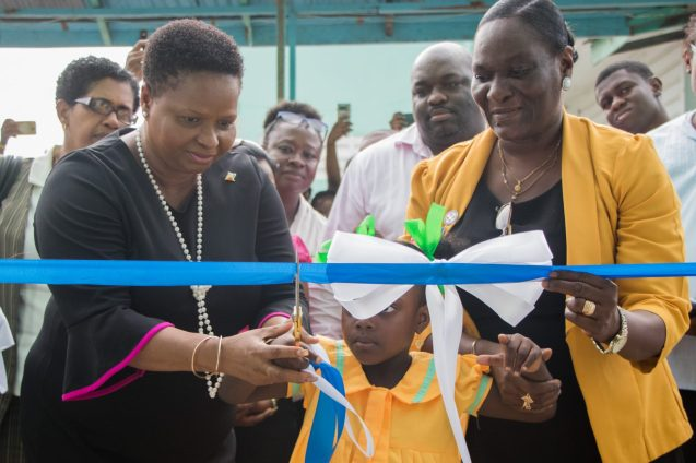 Minister of Public Health Volda Lawrence cuts the ceremonial ribbon with assistance from Senior Nursing Tutor, Oslene Hicken-Paul