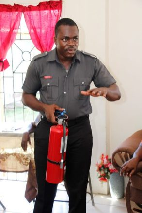 Troy Williamson demonstrating the use of a fire extinguisher.