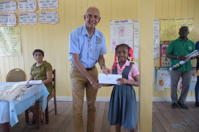 Minister of Communities, Hon. Ronald Bulkan rewards Two Miles Primary School student Faith Peters