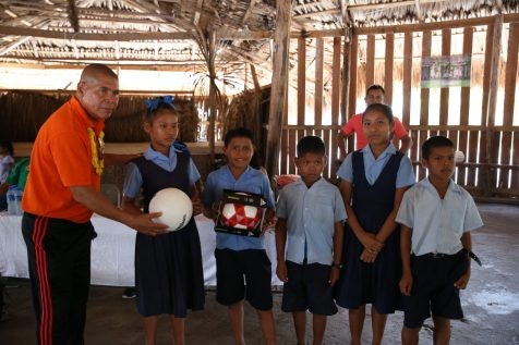 Minister of Social Cohesion Dr George Norton hands over sports gear to children of St. Cuthbert's Mission