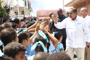 Prime Minister, Moses Nagamootoo, greets school children on his way to cabinet meeting in Bartica, region 7 on Tuesday