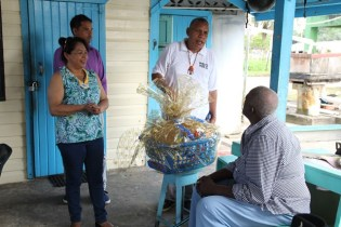 Minister of State, Dawn Hastings-Williams presents a hamper to Roy Benjamin.