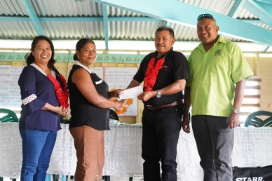 Minister of State, Dawn Hastings-Williams and Minister of Indigenous Peoples' Affairs, Sydney Allicock handing over a cheque to Toshao Sharmine Rambaju in the presence of the Ministry of Indigenous Peoples' Affairs Special Assistant on Projects and Community Development, Martin Cheung.